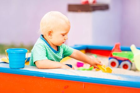 Photo pour Cute baby boy playing with toys in the sandbox outdoor - image libre de droit