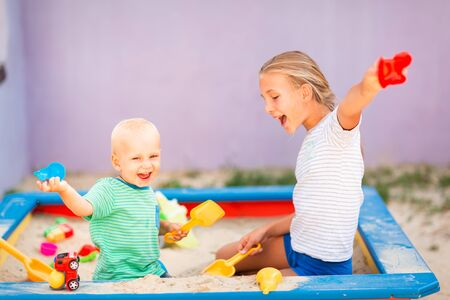 Photo pour Cute baby boy playing with his sister with toys in the sandbox outdoor - image libre de droit