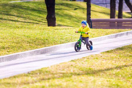 Foto de Happy little boy riding a run-bike in the park outdoor - Imagen libre de derechos
