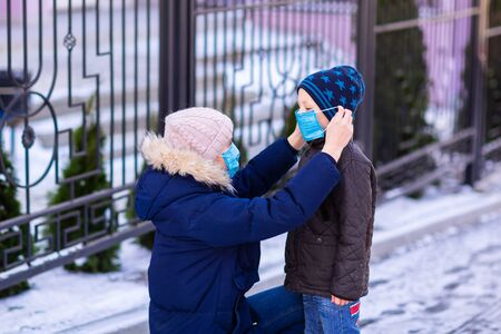 Photo for Young woman wearing medical face mask helping to put on a mask on a little boy for protection from coronavirus on the street outdoor during quarantine. Corona virus, covid -19, pandemic protection concept. - Royalty Free Image