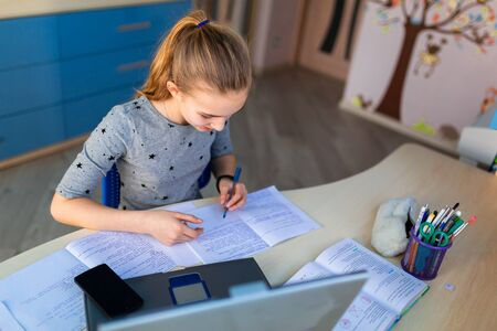 Foto de Beautiful young school girl working at home in her room with a laptop and class notes studying in a virtual class. Distance education and learning, e-learning, online learning concept during quarantine - Imagen libre de derechos