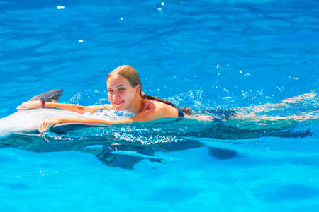 Photo pour Happy little girl swimming with dolphins in Dolphinarium. Swimming, bathing and communication with dolphins. - image libre de droit