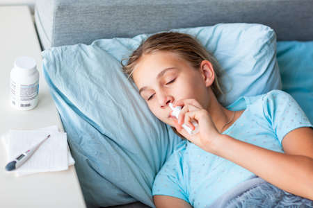 Foto de Sick teenage little girl with high fever and headache laying in bed spraying medicine into her nose. Stay at home during corona virus epidemic if you feel sick - Imagen libre de derechos