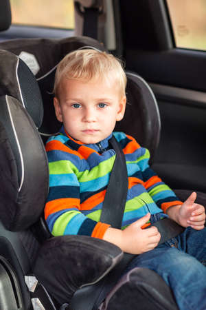 Photo for Little baby boy sitting on a car seat buckled up in the car. Children's Car Seat Safety - Royalty Free Image