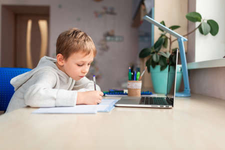Photo pour Cute little schoolboy studying at home doing school homework. Training books and notebook on the table. Distance learning online education - image libre de droit