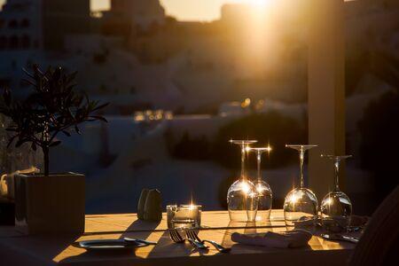 Foto de Restaurant table decorated with glasses on terrace in sunset light on the island Santorini, Cyclades, Greece - Imagen libre de derechos