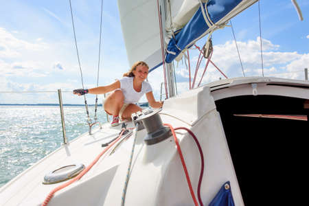 Photo pour Young woman sailing on a yacht. Female sailboat crewmember trimming main sail during sail on vacation in summer season - image libre de droit