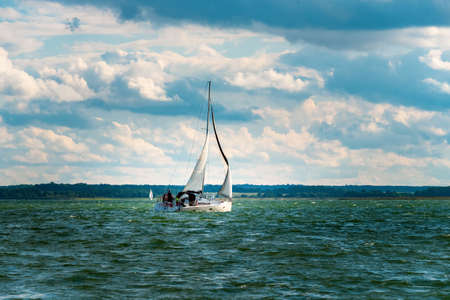 Photo for Sailing yacht in the lake with gloomy sky before the rain and windy weather. Yacht sailing on the lake against a blue sky with clouds. Sailboat vacations on a lake. - Royalty Free Image