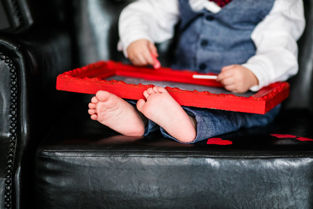 Photo pour Little boy sitting on the armchair with red framed picture on the St. Valentine's day; little feet close-up - image libre de droit