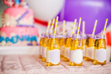 Photo pour Birthday party concept, candy bar for children. A lot of bottles of apple juice, white and yellow straws, big pink cake and white and purple ballons on background - image libre de droit