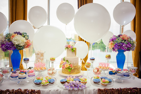 Photo pour Candy bar on golden wedding party with a lot of different candies, cupcakes, souffle and cakes. Decorated in brown and purple colors, nature and eco theme, indoor. - image libre de droit