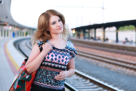 Young woman smiling on train station platform with bags