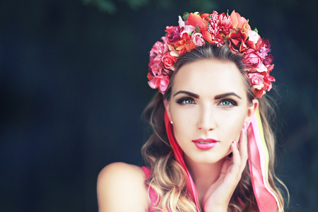 beautiful fairy: filtered image of brunette pretty girl in lotus flower crown and pink makeup posing gracefully on green outdoors copy space backgroundの写真素材