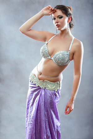 half length portrait of young beautiful belly dancer standing next to color background
