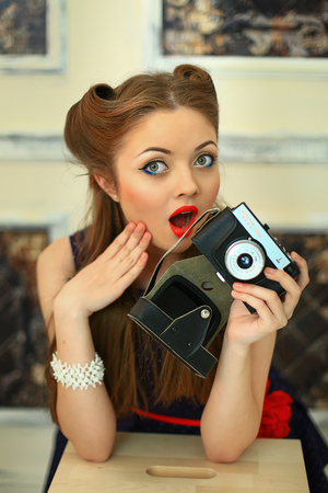 the girl in a dress in peas with red lipstick poses on the camera with the antiquarian camera