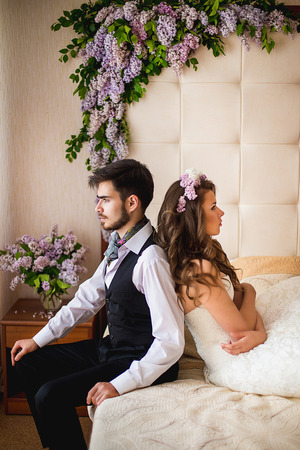 the groom with the bride sit on a bed. Nearby there are a lot of flowers of a lilac