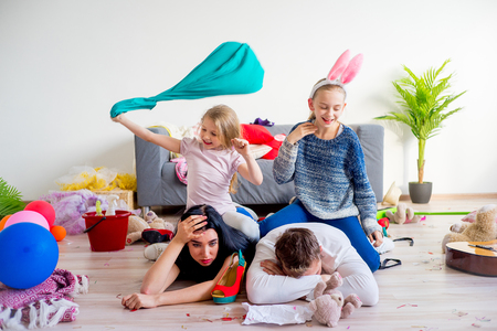 Foto de Tired parents and romping kids - Imagen libre de derechos