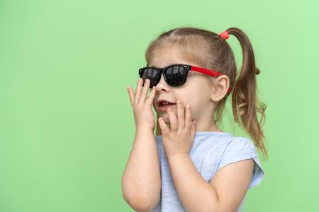 Photo pour little girl 4 years old in a blue T-shirt on a green background in a blue tank top puts on sunglasses and smiles, copy space to the left - image libre de droit