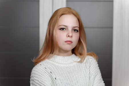 Photo pour portrait of a sad beautiful 16 year old caucasian girl in a white knitted sweater - image libre de droit
