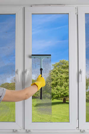 Photo pour Cleaning  modern PVC windows with a hand-held squeegee concept - image libre de droit