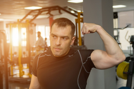 handsome athletic young man showing his biceps posing in gym, sunlight