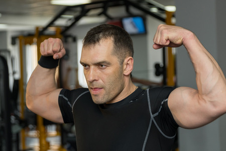 Young muscular man flexing his biceps in gym.