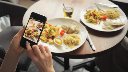 Foto de Woman blogger takes photos of her food in a cafe using mobile phone. Hands with phone screen close-up. - Imagen libre de derechos