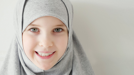 Photo pour Portrait of young attractive muslim 9-years girl wearing grey hijab and traditional dress looking at the camera and smiling on light background, copy space. - image libre de droit