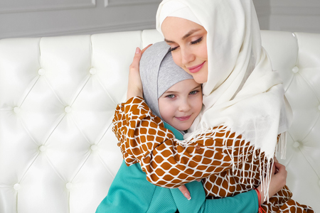 Photo pour Muslim family mom and her little daughter in hijabs are hugging sitting on the sofa at home in modern white interior, side view. - image libre de droit