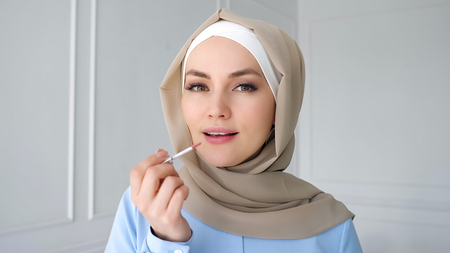 Photo pour Portrait of young muslim woman in beige hijab and traditional blue dress is applying compact powder with sponge on her face looking at small mirror at home, side view. - image libre de droit