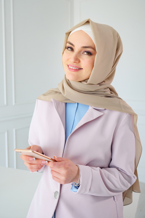 Photo pour Portrait of muslim business woman in beige hijab with mobile phone in office, close-up - image libre de droit