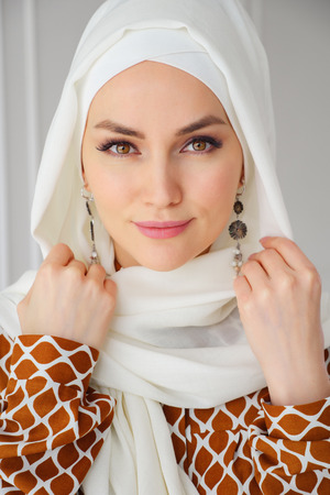 Foto de Portrait of beautiful young muslim arabian woman wearing white hijab looking at camera, close up - Imagen libre de derechos