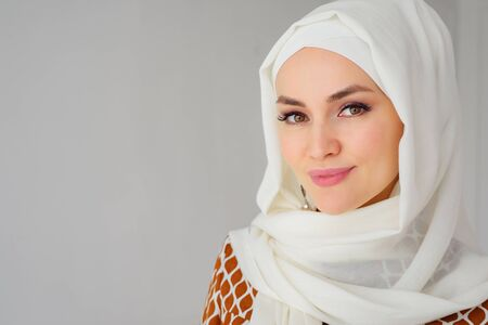 Photo pour Portrait of beautiful young muslim arabian woman wearing white hijab looking at camera, copy space - image libre de droit