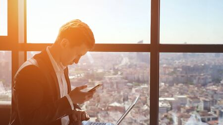 Photo pour Young businessman in suit is working with phone and laptop in office. He is sitting near the window with panoramic city view, copy space - image libre de droit