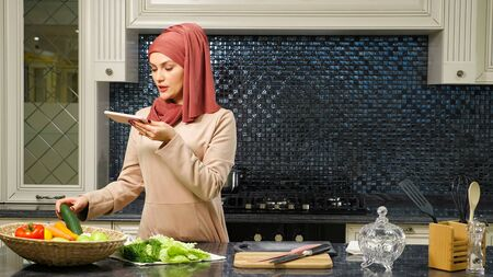 Muslim woman in hijab hosts culinary blog on social network telling subscribers salad recipe in home kitchen close view