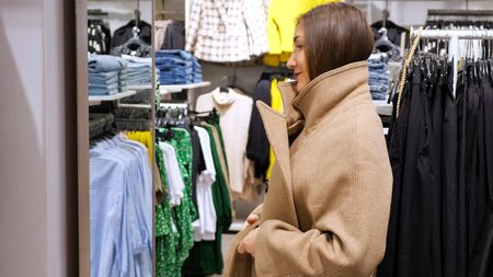 Photo pour Young woman in a long oversize coat in front of a mirror in a store. - image libre de droit