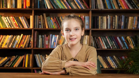 Photo pour Serious young lady in brown dress looks straight and smiles cheerfully to camera sitting at wooden table against library bookshelves - image libre de droit