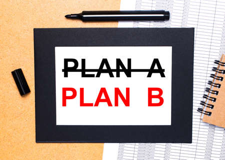 Photo pour On a wooden table, there is a black open marker, a brown notepad and a sheet of paper in a black frame with the text PLAN B. View from above. - image libre de droit