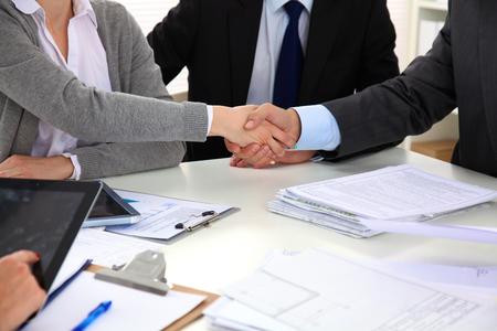 Photo pour Business people shaking hands, finishing up a meeting. - image libre de droit