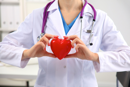 Young woman doctor holding a red heart, in office.