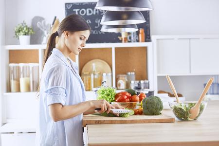 Photo pour A young woman prepares food in the kitchen. Healthy food - vege - image libre de droit