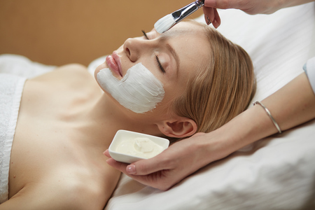 Photo pour people, beauty, cosmetology and treatment concept - close up of beautiful young woman lying with closed eyes and cosmetologist applying facial mask by brush at spa - image libre de droit