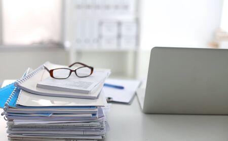 Foto de Laptop with stack of folders on table on white background - Imagen libre de derechos
