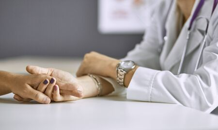 Woman doctor calms patient and holds hand