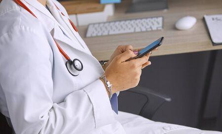 Foto de female doctor between patients in the office talking on the pho - Imagen libre de derechos