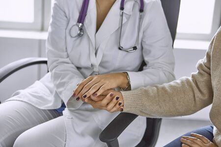Woman doctor calms patient and holds hand.