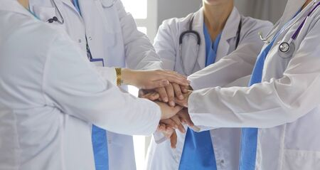 Team of medical workers holding hands together indoors, above view. Unity concept.