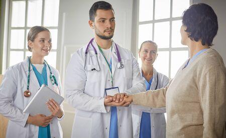 Photo pour Patient with a group of doctors at the background - image libre de droit