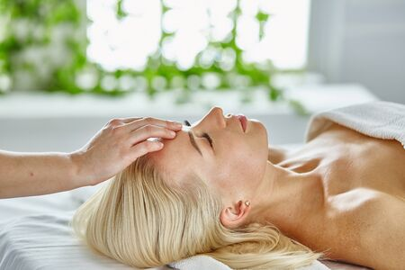 Photo pour Beautiful woman with closed eyes getting a massage in the spa salon. - image libre de droit