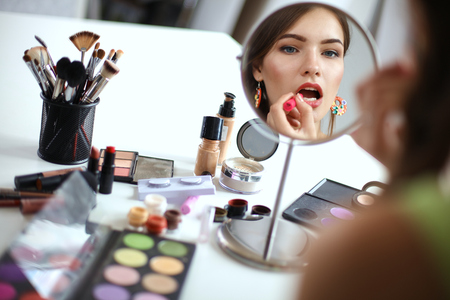 Photo for Young beautiful woman making make-up near mirror,sitting at the desk - Royalty Free Image